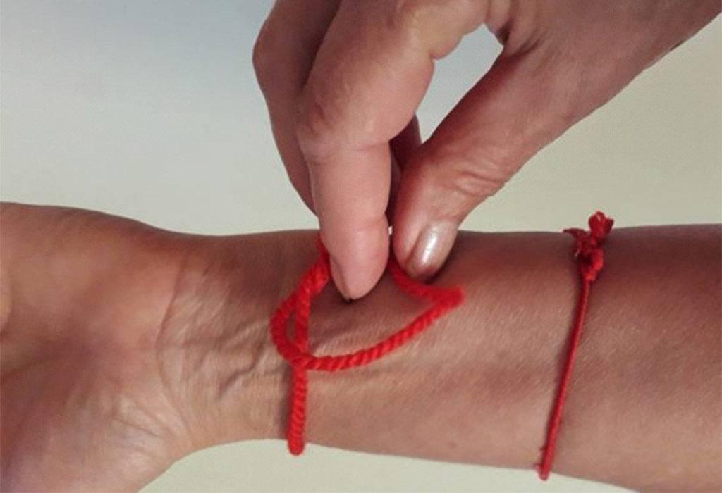 Как правильно завязать красную нить на запястье